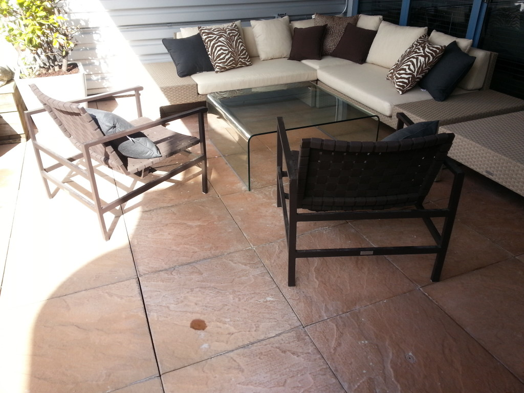 Patio deck red stone tiles returned to like new after SPM deck cleaning service